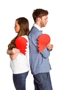 Side view of young couple holding broken heart