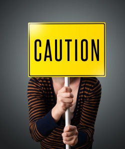 Young woman holding a caution sign